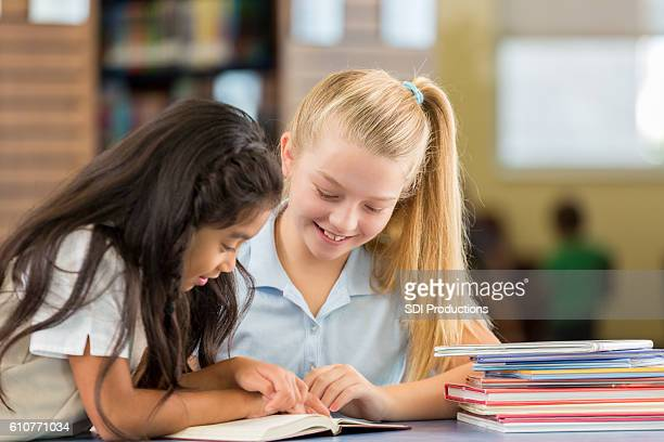 Happy schoolgirls reading books together in the library