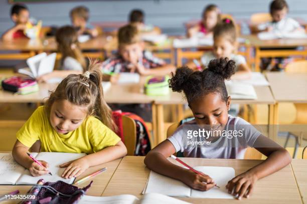 happy schoolgirls writing a dictation on a class at school. - classroom stock pictures, royalty-free photos & images