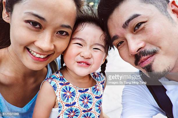 A happy selfie family potriat of three