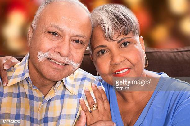 Happy senior adult couple at home with Christmas lights.