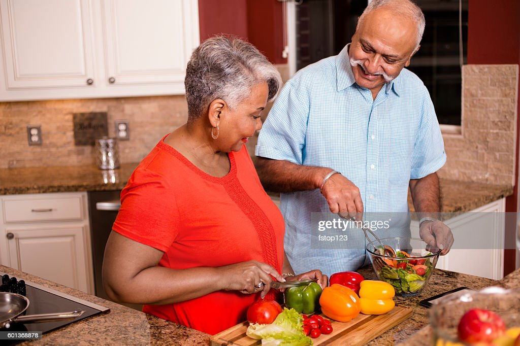 Happy senior adult couple cooking together in home kitchen. : Stock Photo