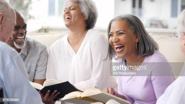 happy senior adult laugh during book club meeting - book club meeting stock pictures, royalty-free photos & images