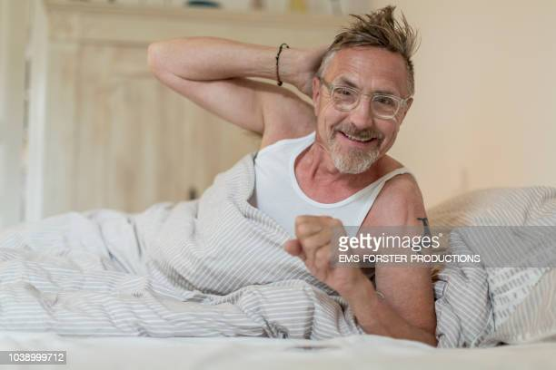 happy senior adult man in his early 60s with grey beard and eyeglasses chilling in bed during day. - 不完全な美しさ ストックフォトと画像