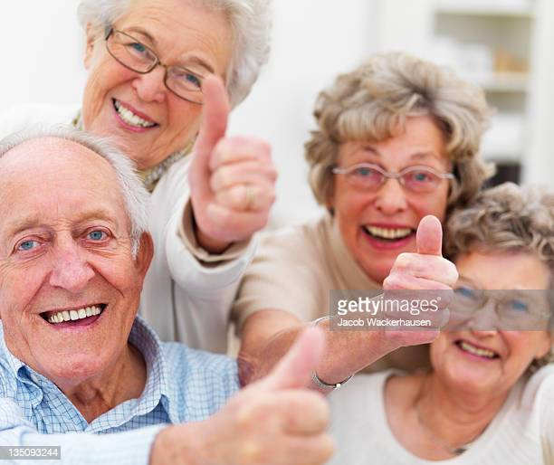 Happy senior adults showing thumbs up sign