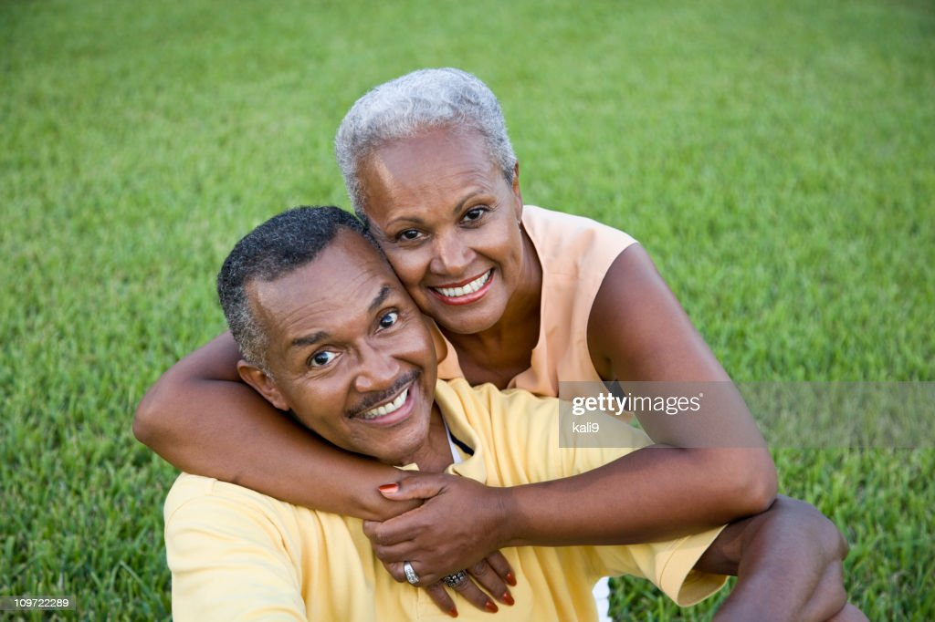 Happy senior African American couple sitting on grass together : Stock Photo