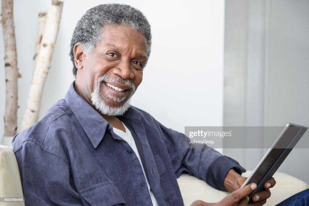 Feliz sênior homem afro-americano com tablet, olhando para a câmera : Foto de stock