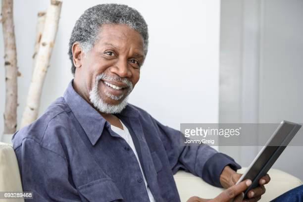 feliz sênior homem afro-americano com tablet, olhando para a câmera - 60 64 anos - fotografias e filmes do acervo
