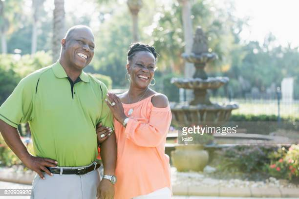 Happy senior African-American couple by fountain