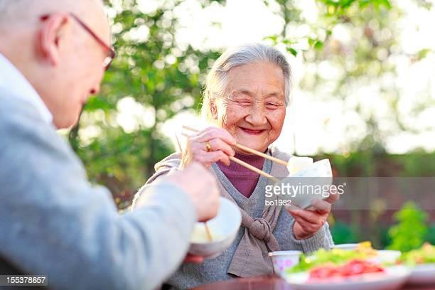 happy senior asian couple having dinner in the garden