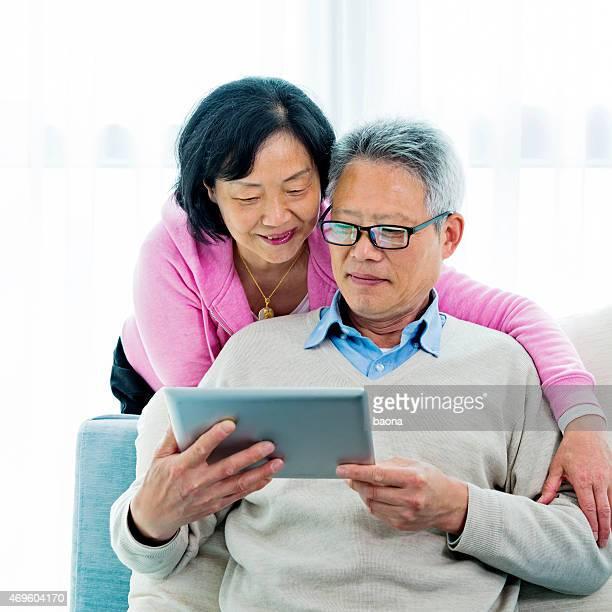 幸せなシニアアジアカップルデジタルタブレットで読書
