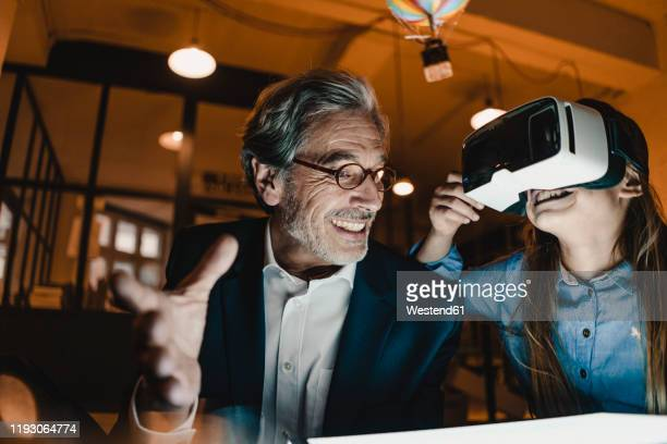 happy senior buisinessman and girl wearing vr glasses with hot-air balloon in office - inventor stock pictures, royalty-free photos & images