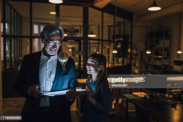 happy senior buisinessman and girl with hot-air balloon and shining tablet in office - contraptie stockfoto's en -beelden