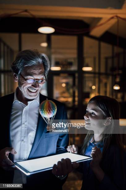 happy senior buisinessman and girl with hot-air balloon and shining tablet in office - inventor stock pictures, royalty-free photos & images