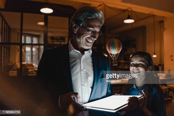 happy senior buisinessman and girl with hot-air balloon and shining tablet in office - directrice stockfoto's en -beelden