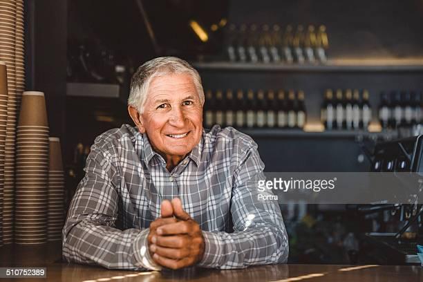 happy senior business owner at cafe - un solo hombre mayor fotografías e imágenes de stock