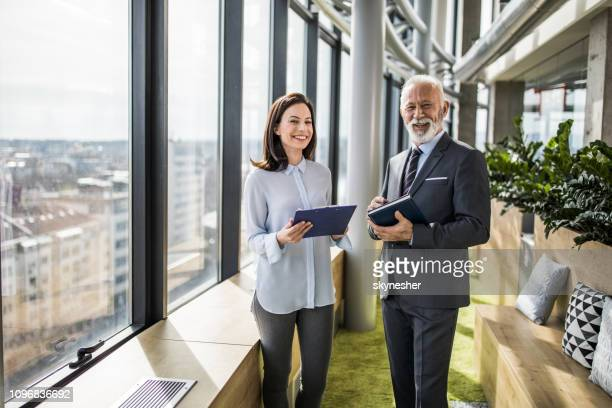 happy senior businessman and his young female colleague in a hallway. - executive director stock pictures, royalty-free photos & images