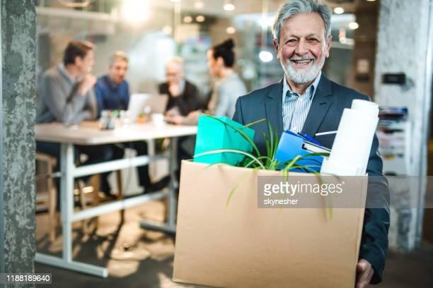 homme d'affaires aîné heureux quittant le bureau avec ses effets personnels. - partir photos et images de collection