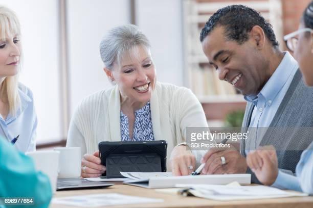 Happy senior businessman reviews document during meeting