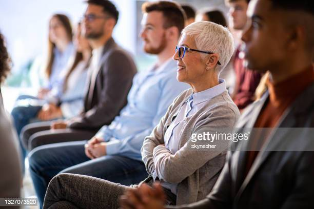 happy senior businesswoman attending a seminar in board room. - attending stock pictures, royalty-free photos & images