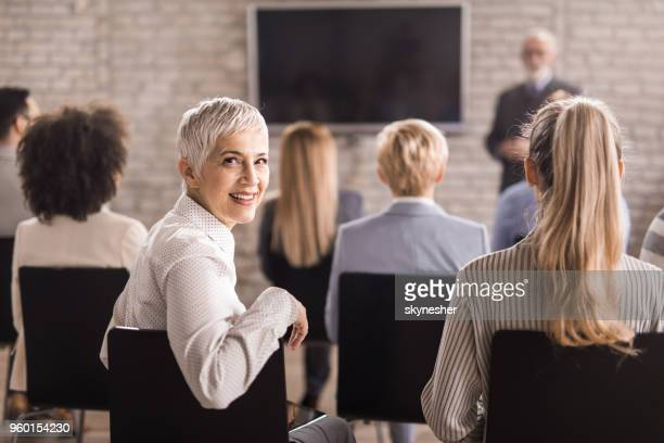 happy senior businesswoman attending a training class in a board room. - attending stock pictures, royalty-free photos & images