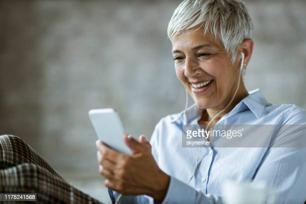happy senior businesswoman listening music over cell phone in the office. - white hair stock pictures, royalty-free photos & images