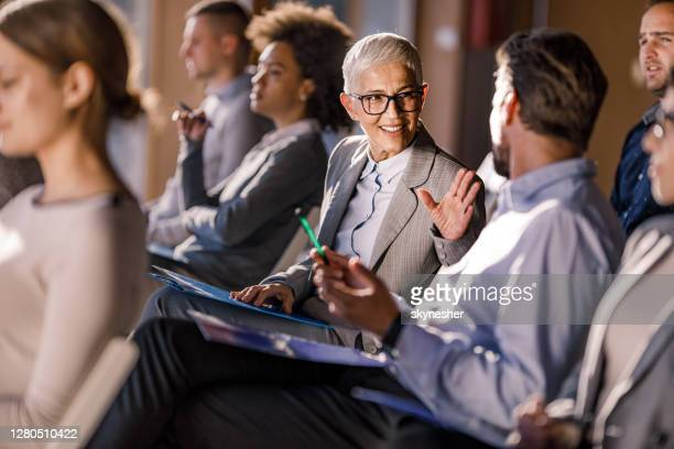 happy senior businesswoman talking to her colleague on a seminar. - conference centre stock pictures, royalty-free photos & images