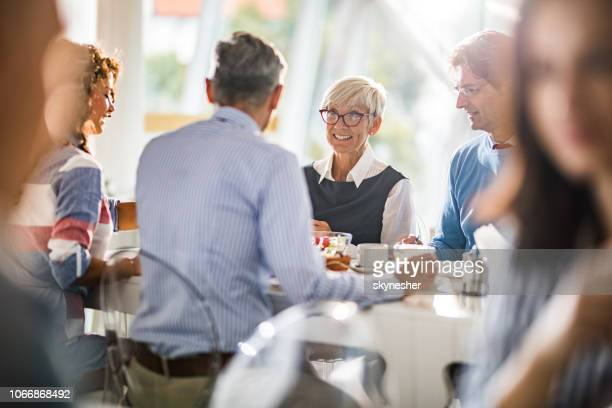 happy senior businesswoman talking to her colleagues on a lunch break. - senior lunch stock photos and pictures