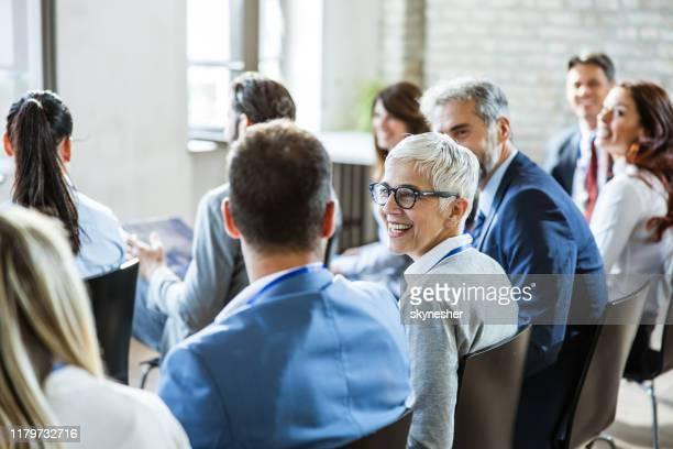 glückliche seniorin im gespräch mit ihren kollegen auf seminar im büro. - vortrag stock-fotos und bilder
