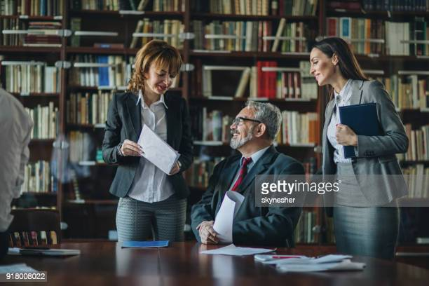 Happy senior CEO going through paperwork with two female colleagues.