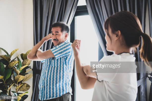 happy senior chinese man doing stretching exercise with daughter in living room - physiology stock pictures, royalty-free photos & images