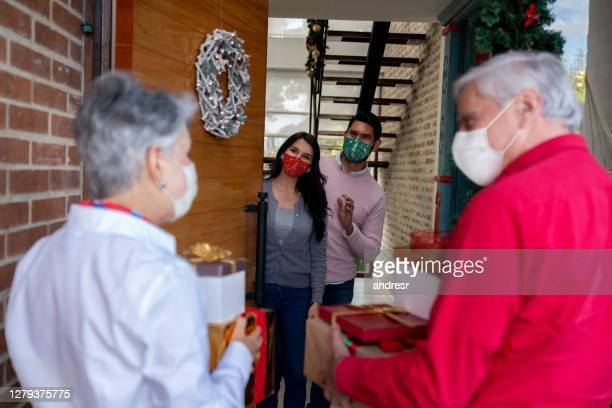 happy senior couple arriving home for christmas wearing facemasks - arrival stock pictures, royalty-free photos & images