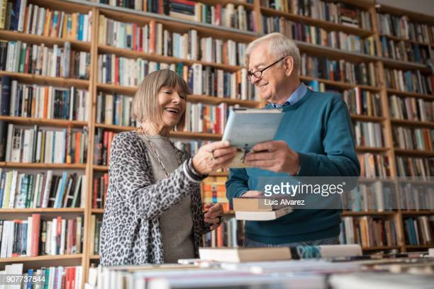 Happy senior couple choosing book at bookstore
