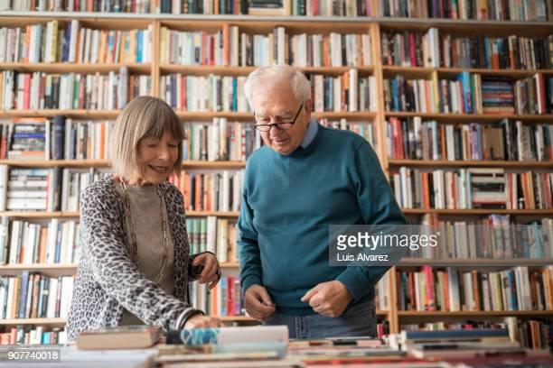 Happy senior couple choosing book