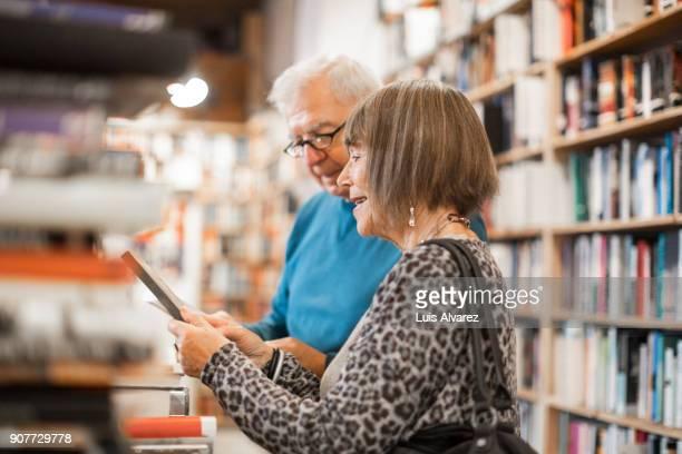 Happy senior couple choosing books
