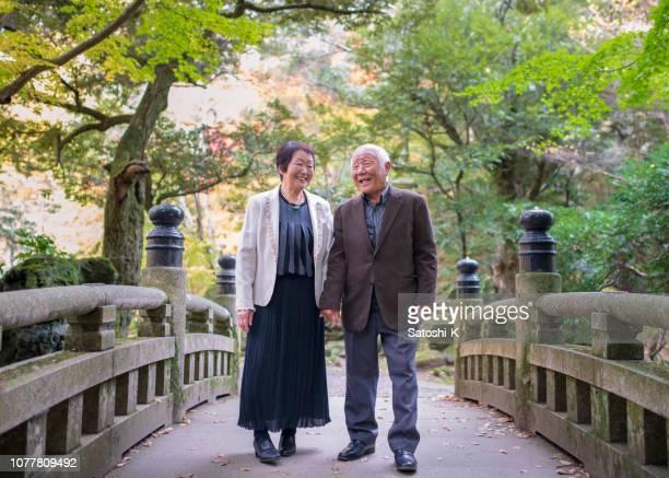 happy senior couple crossing bridge in public park - narita stock pictures, royalty-free photos & images