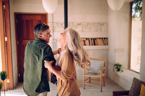 Happy senior couple dancing and laughing together at home 996990764
