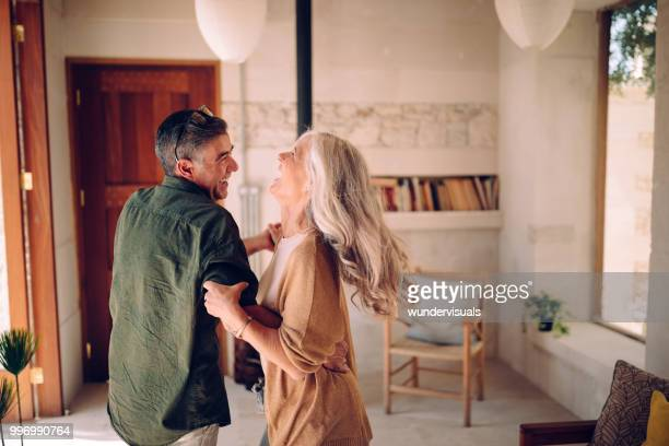 happy senior couple dancing and laughing together at home - felicità foto e immagini stock