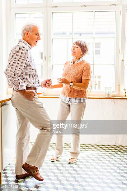 Happy senior couple dancing at kitchen