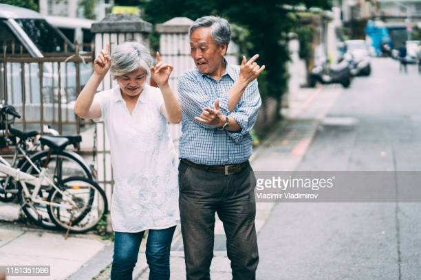 happy senior couple dancing on street - young at heart stock pictures, royalty-free photos & images