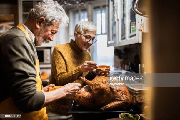 happy senior couple decorating turkey on thanksgiving day. - thanksgiving decoration stock pictures, royalty-free photos & images