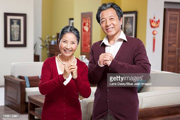 Happy senior couple doing Chinese New Year greeting