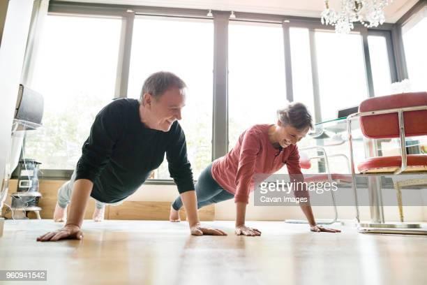 happy senior couple doing push-ups at home - krafttraining stock-fotos und bilder