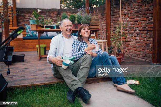 Happy senior couple drinking coffee in the garden