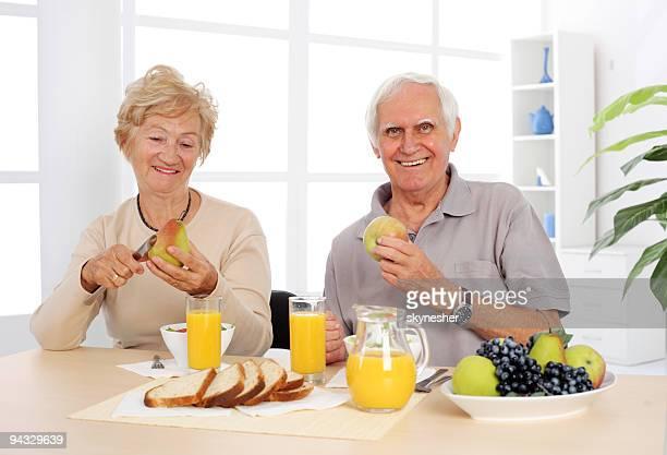 Happy senior couple eating healthy breakfast.