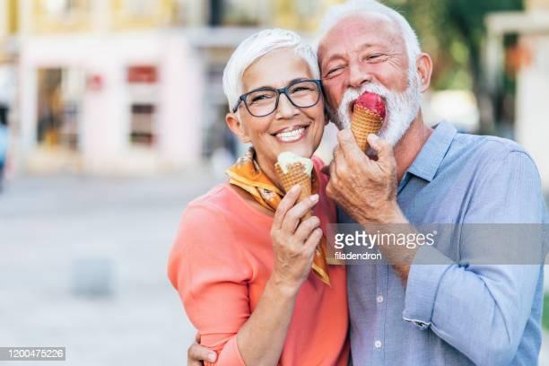 glückliches senior-paar isst eis - eis essen stock-fotos und bilder