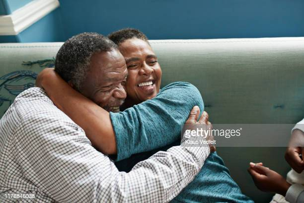 Happy senior couple embracing on sofa at home