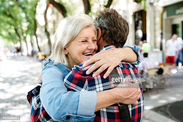 happy senior couple embracing on the street - wiedersehenstreffen stock-fotos und bilder