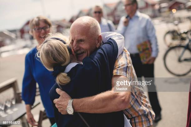 Happy senior couple embracing with friends in background during summer vacation