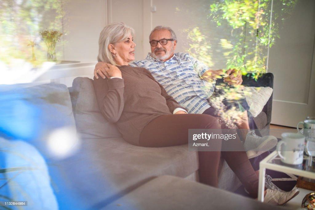 Happy senior couple enjoying coffee on sofa : Stock Photo