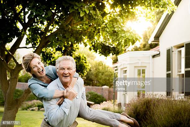 Happy senior couple enjoying in yard on sunny day